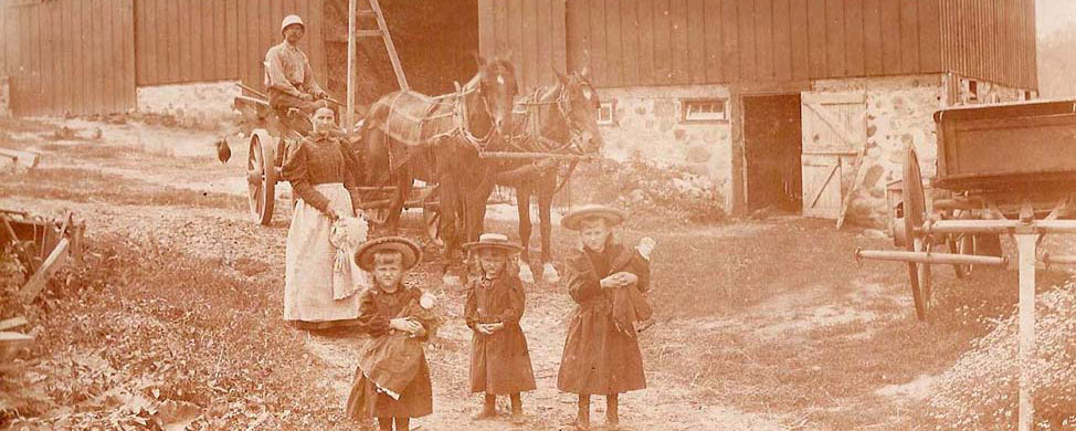 family in front of barn, circa 1900